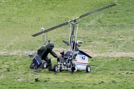 A Member of a Bomb Squad Works Beside a Bomb Disposal Robot (c) and a Gyrocopter (r) After It Landed on the West Front of the Us Capitol on Capitol Hill in Washington Dc Usa 15 April 2015 a Small Gyrocopter Landed on the Lawn of the Us Capitol on 15 April and Police Took the Pilot Into Custody the Us Capitol Police Said the Area Around the Small Rotary Aircraft Had Been Closed Down Police Said Television Images Showed a Police Robot Examining the Craft Which Looked Like a Flying Motorcycle where the Pilot Sits in the Open Air the Tail of the Aircraft was Emblazoned with the Us Postal Service Logo According to a Florida Newspaper the Pilot was Doug Hughes a 61-year-old Mailman United States Washington