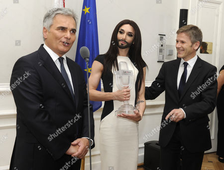 Austrian Singer Conchita Wurst (thomas Neuwirth - C) Winner of the Eurovision Song Contest 2014 and the Minister For Cultural Affairs Josef Ostermayer (r) Listen to Austrian Chancellor Werner Faymann (l) During a Reception at the Chancellor's Office in Vienna Austria 18 May 2014 Austria Vienna