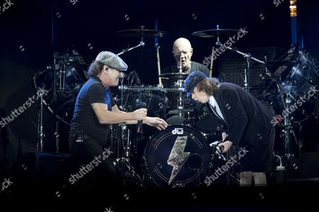 (l-r) British-born Lead Singer Brian Johnson British Drummer Chris Slade and Scottish-born Australian Lead Guitarist Angus Young of the Band Ac/dc Perform on Stage During a Concert in Spielberg Austria 14 May 2015 Austria Spielberg