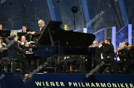 Stock Photo of The Vienna Philharmonic Orchestra with Indian Conductor Zubin Mehta (2-l) and Austrian Pianist Rudolf Buchbinder (l) Perform During the Open Air Concert 'Sommernachtskonzert' (lit: Summer Night Concert) at the Schoenbrunn Palace in Vienna Austria 14 May 2015 Austria Vienna