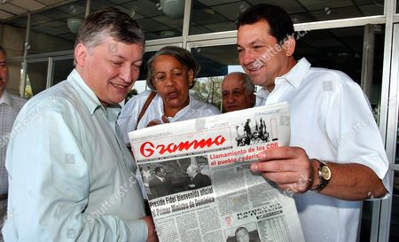 Cuban President of the Institute of Sports Humberto Rodriguez (r) Shows the Official Newspaper to Russian Chess Champion Anatoli Karpov After His Arrival on Tuesday 27 April 2004 to Havana City Karpov Will Participate in a Giant Simoultaneous Chess Competition in Which Cuba Will Try to Beat Its Own Guiness Record the Country Got Two Years Ago Cuba Havana City