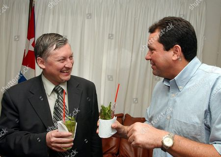 Stock Photo of Russian Chess Player Anatoli Karpov (l) Holds a Glass of Cuban Mojito and Talks with Humberto Rodriguez (r) Cuban Sport Institute President in Havana Monday 26 April 2004 Karpov Four Times Chess World Champion Will Participate in a Giant Simultaneous Match on 29 April when Cuba Will Try to Break Its Own Guinness Record Cuba La Habana