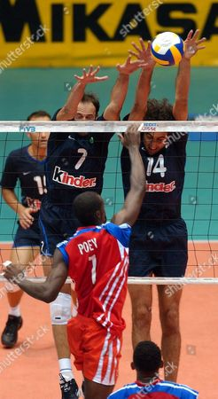 Italian Players Andrea Sartoretti (l) and Alessandro Frei (r) Block an Attack of Cuban Raydel Poey (c) During the Match of the Volleyball World League Held Friday 2 July 2004 at Havana Cuba Italia Won the Game by 3-2 Sets Cuba Havana