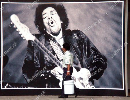 A Worker Carries Buckets Past a Poster of '60s Rock Icon Jimi Hendrix on Wednesday 14 January 2004 in the National Auditorium of Mexico City Prior to a Press Conference by 66-year-old American Photographer Baron Wolman Introducing His Exhibition 'I Saw the Music' Wolfman Presented More Than 50 Images of Such Well-known Musicians As Jimi Hendrix the Grateful Dead and Janis Joplin One of His Pictures of Hendrix is Featured on the Poster Mexico Ciudad De M?xico