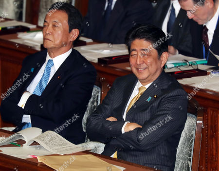 Japanese Prime Minister Shinzo Abe (R) accompanied by Finance Minister Taro Aso (L) listens to questions by the main opposition Democratic Party Secretary General Yoshihiko Noda for Abe's policy speech at the Lower House's plenary session at the National Diet in Tokyo