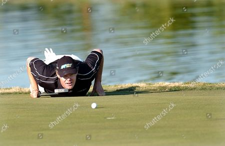 Sweden's Joakim Haeggman Lies Down on the Green While Lining Up a Putt on the 18th Hole During the First Day of the World Cup Golf Championships at the Real Club De Golf in Seville Spain Thursday 18 November 2004 Spain Seville