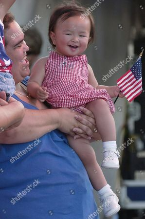 Megan Medina Holds Maia Medina 13 Month Adopted From China As the Vows of Allegiance Are Pledged During a Us Citizenship Ceremony That was Followed by a Concert Featuring Julio Iglesias Jr and a Fireworks Display Sunday 04 July 2004 at Lummus Park on Ocean Drive Miami Fl United States Miami