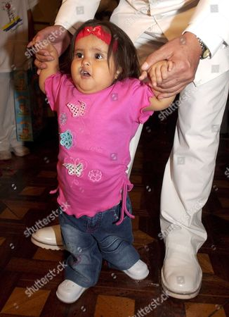 Stock Picture of Peruvian Mermaid Girl Milagros Cerron Walks with the Help of Lima's Mayor Luis Castaneda Lossio on the Day of Her Second Birthday Thursday 27 April 2006 in the Peruvian Capital 'Milagritos' Will Undergo Surgery on 25 May 2006 to Have the Upper Part of Her Legs Separated Peru Lima