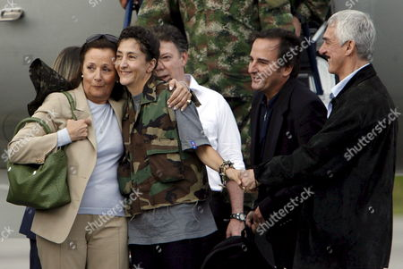 Colombian-french Former Presidencial Candidate Ingrid Betancourt (c) Hugs Her Mother Yolanda Pulecio (l) Along with Her Husband Juan Carlos Lecompte (2-r) Upon Her Arrival to the Militar Airport of Catam in Bogota Colombia on 02 July 2008 After Being Rescued by the Colombian Army in the Jungle of the Eastern Department of Guaviare After a Long Hostage by the Farc Guerrilla with Betancourt Also was Rescued the Three Us Citizens and Other 11 Colombian Military Troops Colombia Tolemaida