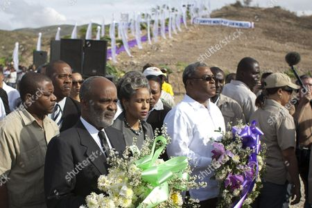The Haitian President Rene Preval (l) His Wife Elisabeth Preval (c) and the Haitian Prime Minister Jean Max Bellerive (r) Carry Flower Ornaments During a Conmemoration of the First Anniversary of the Haitian Earthquake Celebrated in St Christophe Titanyen Haiti 11 January 2011 the Conmemoration Took Place at the Site of a Mass Grave where Many of the Victims of the Earthquake Are Buried Haiti Port Au Prince