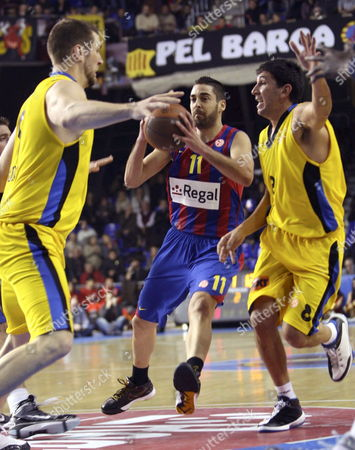 Regal F C Barcelona's Point Guard Juan Carlos Navarro (c) Fights For the Ball Between Maroussi's Us Power Forward Jared Homan (l) and Point Guard Marios Batis (r) During Their Top 16 Euroleague Match at the Palau Blaugrana in Barcelona Northeastern Spain on 28 January 2010 Spain Barcelona