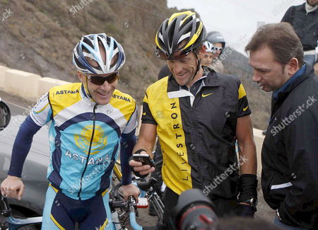 Astana's Us Riders Lance Amstrong (c) and Levi Leipheimer (l) Check a Mobile Phone in Presence of Their Team Director Belgian Johan Bruyneel (r) During a Break of the Training Session of the Team in Tenerife Canary Islands Spain 05 December 2008 Spain Arona (tenerife)