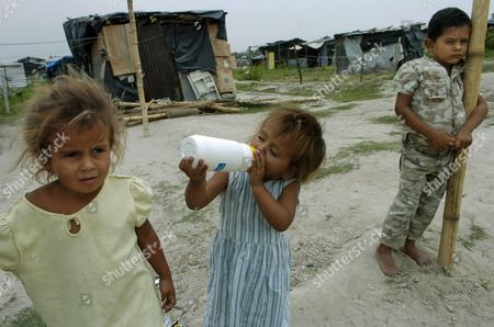 Stock Photo of Four-year-old Iris Beltran (l) Her Three-year-old Sister Maria (c) and Six-year-old Brother Henry (r) Are Seen in Soyapango on the Outskirts of San Salvador El Salvador 19 May 2008 where Nearly 2 000 Salvadorians Have Their Homes the Land a Former Dump and the Precarious Conditions Are the Reflection of the Extreme Poverty and Lack of Housing in This Country El Salvador Soyapango