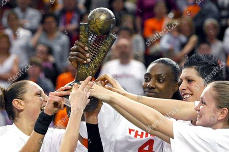 Stock Image of Spartak Moscow's Players Diana Tarurasi (l) Us Pivots Sylvia Fowles (2l) and Janel Mc Carville (2r) and Russian Guard Anastasia Anderson (r) Hold the Trophy As They Celebrate After Winning Against Ros Casares the Euroleague Women's Basketball Final Match at Fuente De San Luis Pavillion in Valencia Eastern Spain 11 April 2010 Spain Valencia