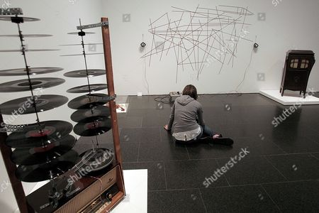 A Young Woman Sits on the Floor As She Observes and Listens to an Interactive Work Created by Us Composer John Cage (1912-1982) in an Exhibition at Barcelona's Contemporanean Art Museum (macba ) in Barcelona City Northern Spain 21 October 2009 the Piano (front) was Customized by Cage with Screws Rubbers and Pencils So As to Get Percussion Sounds As Well As the Ones Made by a Traditional Piano the Exposition Titled 'The Anarchy of Silence John Cage and Experimental Art' is the World's Biggest Dedicated to Cage Since His Death and Also Displays Works of Art by Duchamp Warhol Rauschenberg Nam June Paik and Fluxus It Runs From 23 October 2009 to 10 January 2010 Spain Barcelona