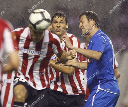 Athletic Bilbao's Defender Aitor Ocio (l) Heads the Ball Next to Estonian Joel Lindpere (r) of Tromsoe During Their Play Offs First Leg Qualifying of the Europa League Soccer Match at San Mames Stadium in Bilbao Basque Country Northern Spain 20 August 2009 Spain Bilbao