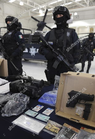 Stock Photo of Mexican Federal Police Officers Show on 05 August 2010 at the Central Police Command in Mexico City the Weapons That Were Confiscated From Oscar Gutierrez (l) Gilberto Cervantes (c) and Jesus Villa (r) Alleged Kidnappers of Three Journalist the Suspects Were Captured Last Wednesday Mexico Mexico City
