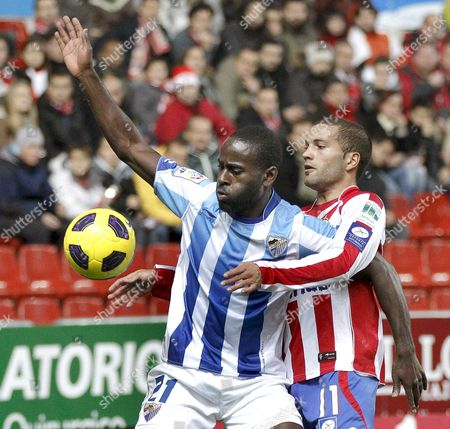 Stock Picture of Malaga's Ghanaian Forward Quincy Owusu-abeyie (l) Vies For the Ball with Defender Alberto Lora (r) of Sporting Gijon During Their Spanish Primera Division Soccer Match at El Molinon Stadium in Gijon Asturias Northern Spain 02 January 2011 Spain Gijon