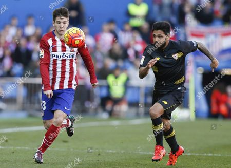 Stock Image of Atletico Madrid's Argentinian Striker Luciano Vietto (l) Fights For the Ball with French Defender Benoit Tremoulinas (r) of Sevilla Fc During Their Primera Division Soccer Match Played at Vicente Calderon Stadium in Madrid Spain on 24 January 2016 Spain Madrid