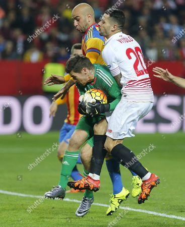 Valencia's Australian Goalie Mark Ryan (c) Catches the Ball in Presence of Sevilla's Vitolo (r) During Their Spanish Primera Division Soccer Match at Sanchez Pizjuan Stadium in Seville Spain 29 November 2015 Spain Sevilla