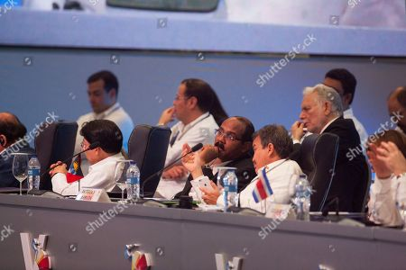 Minister Gaston Browne from Antigua and Barbuda, center, listens to Cuban President Raul Castro speak to the heads of state at the V Summit of the Community of Latin American and Caribbean States in Bavaro, Dominican Republic, . Foreign Minister Carl B. Greenidge of Guyana sits to his left