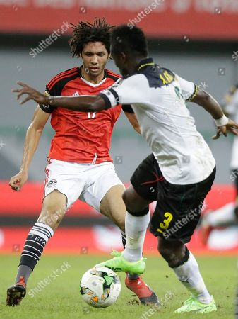Stock Picture of Egypt's Mohamed Elneny, left, is challenged by Ghana's, Asamoah Gyan during their African Cup of Nations Group D soccer match at the Stade de Port-Gentil in Port-Gentil, Gabon
