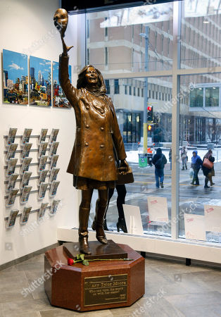 """A single rose sits by the life-size bronze statue of Mary Tyler Moore at the Minneapolis Visitor Center, . Moore, 80, died Wednesday. The statue depicts her tossing her tam into the air as she did in the opening credits of """"The Mary Tyler Moore Show"""