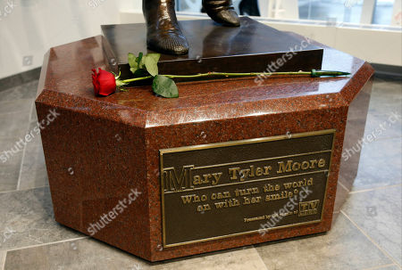 """A single rose sits on the base of the life-size bronze statue of Mary Tyler Moore at the Minneapolis Visitor Center, . Moore, 80, died Wednesday. The statue depicts her tossing her tam into the air as she did in the opening credits of """"The Mary Tyler Moore Show"""