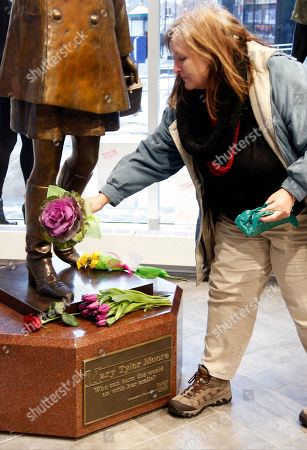 """Stock Picture of Betty Murphy of Detroit places flowers at the base of the life-size bronze statue of Mary Tyler Moore at the Minneapolis Visitor Center Wednesday, Jan.25, 2017. Moore, 80, died Wednesday. The statue depicts her tossing her tam into the air as she did in the opening credits of """"The Mary Tyler Moore Show"""" which featured Mary Richards working for a Minneapolis television station"""