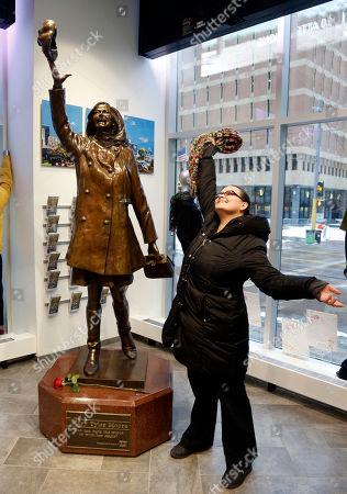"""A fan who wanted to remain anonymous strikes a pose by the life-size bronze statue of Mary Tyler Moore at the Minneapolis Visitor Center . Moore, 80, died Wednesday. The statue depicts her tossing her tam into the air as she did in the opening credits of """"The Mary Tyler Moore Show"""