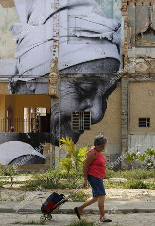 A Woman Walks Past a Giant Photograph by Cuban-us Artist Jose Parla Adorning the Wall of a Building As Part of the Xi Art Biennale in Havana Cuba 11 May 2012 Cuba Havana