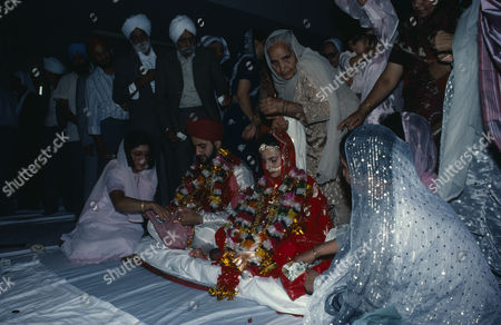 Bride and groom receiving gifts of money from guests during wedding ceremony.
