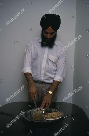 Sikh man using short knife or kirpan to bless food.