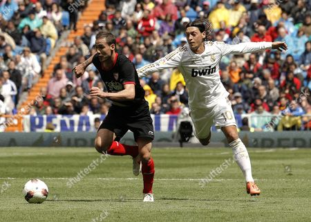 Real Madrid's German Midfielder Mesut Oezil (r) Fights For the Ball with Sevilla's Omar Rodriguez 'Deivid' During Their Spanish Primera Division Soccer Match Against Held at Santiago Bernabeu Stadium in Madrid Spain 29 April 2012 Spain Madrid