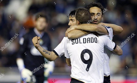 Valencia's Brazilian Striker Jonas Goncalves (r) Celebrates with His Teammates Roberto Soldado (front) and Dani Parejo (l) After Scoring the Opening Goal During the Spanish Primera Division Soccer Match Between Valencia Cf and Real Betis at Mestalla Stadium in Valencia City Eastern Spain 22 April 2012 Spain Valencia
