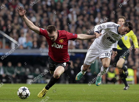 Manchester United's Midfielder Philip Jones (l) Fights For the Ball with Real Madrid German Mesut Oezil (r) During Their Champions League's Round of 16 First Leg Match at Santiago Bernabeu Stadium in Madrid Spain 13 February 2013 Spain Madrid