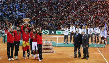 Spanish Tennis Players (l) Celebrate with the Davis Cup Trophy in Front of Argentina's Team (back R) As Spain's King Juan Carlos Ii (2nd R) and Tennis International Federation President Francesco Ricci Bitti (r) Look on After the Last Match of the Davis Cup Final Between Spain and Argentinaat the Olympic Stadium in Seville Southern Spain 04 December 2011 Nadal Won 1-6 6-4 6-1 and 7-6 (0) and Achieved the Fifth Davis Cup Title For Spain Spain Seville