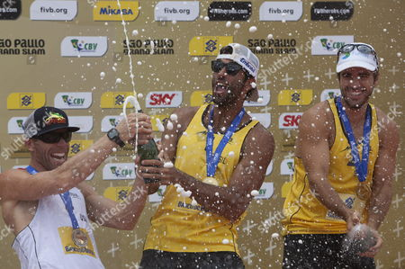 Brazilian Players Bruno Schmidt (r) and Pedro Solberg (c) Celebrate Their Victory Against Us Phil Dalhausser and Casey Jennings at the Final Match From the Fivb Beach Volleyball World Tour Grand Slam in Sao Paulo Brazil 13 October 2013 Us Casey Jennings (l) Accompanies Them on the Podium Brazil Sao Paulo