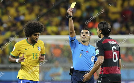 Brazil's Dante (l) is Shown the Yellow Card by Referee Marco Rodriguez During the Fifa World Cup 2014 Semi Final Match Between Brazil and Germany at the Estadio Mineirao in Belo Horizonte Brazil 08 July 2014 (restrictions Apply: Editorial Use Only not Used in Association with Any Commercial Entity - Images Must not Be Used in Any Form of Alert Service Or Push Service of Any Kind Including Via Mobile Alert Services Downloads to Mobile Devices Or Mms Messaging - Images Must Appear As Still Images and Must not Emulate Match Action Video Footage - No Alteration is Made to and No Text Or Image is Superimposed Over Any Published Image Which: (a) Intentionally Obscures Or Removes a Sponsor Identification Image; Or (b) Adds Or Overlays the Commercial Identification of Any Third Party Which is not Officially Associated with the Fifa World Cup) Brazil Belo Horizonte