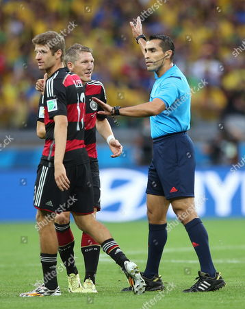 Refereee Marco Rodriguez (r) Talks to German Players Thomas Mueller (l) and Bastian Schweinsteiger During the Fifa World Cup 2014 Semi Final Match Between Brazil and Germany at the Estadio Mineirao in Belo Horizonte Brazil 08 July 2014 (restrictions Apply: Editorial Use Only not Used in Association with Any Commercial Entity - Images Must not Be Used in Any Form of Alert Service Or Push Service of Any Kind Including Via Mobile Alert Services Downloads to Mobile Devices Or Mms Messaging - Images Must Appear As Still Images and Must not Emulate Match Action Video Footage - No Alteration is Made to and No Text Or Image is Superimposed Over Any Published Image Which: (a) Intentionally Obscures Or Removes a Sponsor Identification Image; Or (b) Adds Or Overlays the Commercial Identification of Any Third Party Which is not Officially Associated with the Fifa World Cup) Brazil Belo Horizonte