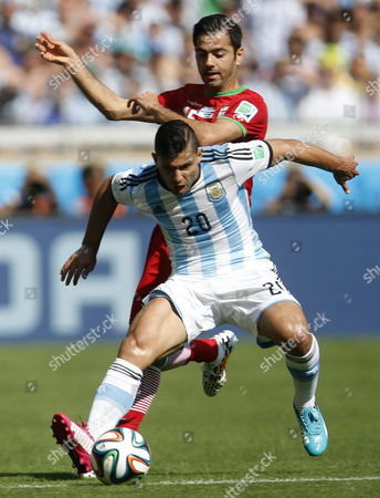 Sergio Aguero (front) of Argentina in Action with Pejman Montazeri of Iran During the Fifa World Cup 2014 Group F Preliminary Round Match Between Argentina and Iran at the Estadio Mineirao in Belo Horizonte Brazil 21 June 2014 (restrictions Apply: Editorial Use Only not Used in Association with Any Commercial Entity - Images Must not Be Used in Any Form of Alert Service Or Push Service of Any Kind Including Via Mobile Alert Services Downloads to Mobile Devices Or Mms Messaging - Images Must Appear As Still Images and Must not Emulate Match Action Video Footage - No Alteration is Made to and No Text Or Image is Superimposed Over Any Published Image Which: (a) Intentionally Obscures Or Removes a Sponsor Identification Image; Or (b) Adds Or Overlays the Commercial Identification of Any Third Party Which is not Officially Associated with the Fifa World Cup) Brazil Belo Horizonte