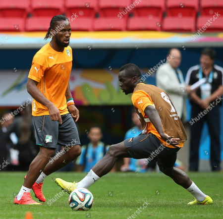 Stock Image of Players Drogba (l) and Ya Konan of the Ivory Coast During Their Team's Training Session in Brasilia Brazil 18 June 2014 Ivory Coast Faces Colombia in the Fifa World Cup 2014 Group C Preliminary Round Match in Brasilia on 19 June 2014 (restrictions Apply: Editorial Use Only not Used in Association with Any Commercial Entity - Images Must not Be Used in Any Form of Alert Service Or Push Service of Any Kind Including Via Mobile Alert Services Downloads to Mobile Devices Or Mms Messaging - Images Must Appear As Still Images and Must not Emulate Match Action Video Footage - No Alteration is Made to and No Text Or Image is Superimposed Over Any Published Image Which: (a) Intentionally Obscures Or Removes a Sponsor Identification Image; Or (b) Adds Or Overlays the Commercial Identification of Any Third Party Which is not Officially Associated with the Fifa World Cup) Brazil Brasilia