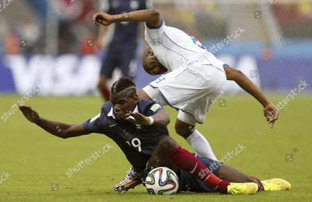 Paul Pogba (down) of France in Action with Wilson Palacios of Honduras During the Fifa World Cup 2014 Group E Preliminary Round Match Between France and Honduras at the Estadio Beira-rio in Porto Alegre Brazil 15 June 2014 (restrictions Apply: Editorial Use Only not Used in Association with Any Commercial Entity - Images Must not Be Used in Any Form of Alert Service Or Push Service of Any Kind Including Via Mobile Alert Services Downloads to Mobile Devices Or Mms Messaging - Images Must Appear As Still Images and Must not Emulate Match Action Video Footage - No Alteration is Made to and No Text Or Image is Superimposed Over Any Published Image Which: (a) Intentionally Obscures Or Removes a Sponsor Identification Image; Or (b) Adds Or Overlays the Commercial Identification of Any Third Party Which is not Officially Associated with the Fifa World Cup) Epa/jorge Zapata Editorial Use Only Brazil Porto Alegre