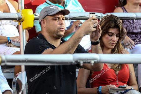 Stock Photo of Former Brazilian Player Ronaldo Luis Nazario De Lima (l) Takes Pictures During the Atp 500 Final Match Between Spaniard Rafael Nadal and Ukranian Alexandr Dolgopolov at Rio De Janeiro Open in Brazil 23 Febraury 2014 Woman on Right is not Identified Brazil Rio De Janeiro