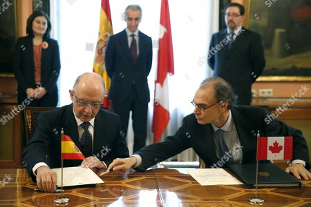 Stock Image of Spanish Treasury Minister Cristobal Montoro (l) and Canadian Ambassador to Spain Jon Allen (r) Sign a New Agreement Between Spain and Canada in Madrid Spain 18 November 2014 Montoro and Allen Have Signed the Protocol That Changes the Agreement Between Both Countries to Avoid the Double Taxation and to Prevent the Tax Evasion and Which Replaces the Agreement Signed in Ottawa in 1976 in Force From December 1980 Spain Madrid