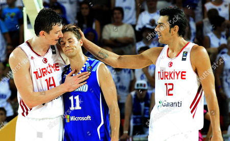 Turkish Players Omer Asik (l) and Kerem Gonlum (r) Comfort Finnish Petteri Koponen (c) After His Team's Defeat in the Fiba Basketball World Cup Match Group C Match Between Turkey and Finland Played at Bizkaia Arena (bec) Pavilion in Bilbao Northern Spain 03 September 2014 Spain Bilbao