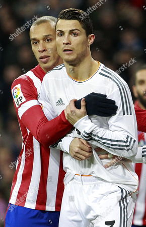 Real Madrid's Portuguese Striker Cristiano Ronaldo (r) and Atletico Madrid's Brazilian Defender Joao Miranda De Souza (l) in Action During the King's Cup Semi-final First Leg Soccer Match Between Real Madrid and Atletico Madrid Played at Santiago Bernabeu Stadium in Madrid Spain 05 February 2014 Spain Madrid