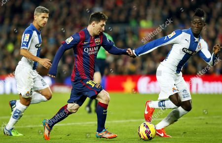 Fc Barcelona's Argentinian Striker Lionel Messi (c) in Action Against Rcd Espanyol Players Salva Sevilla (l) and Eric Bertrand Bailly (r) During the Spanish Primera Division Soccer Match Between Fc Barcelona and Rcd Espanyol at Camp Nou in Barcelona Spain 07 December 2014 Spain Barcelona