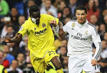 Real Madrid's Cristiano Ronaldo (r) Fights For the Ball with Villarreal's Eric Bertrand Bailly (l) During the Spanish Primera Division Soccer Match Between Real Madrid and Villarreal Cf at Santiago Bernabeu Stadium in Madrid Spain 01 March 2015 Spain Madrid