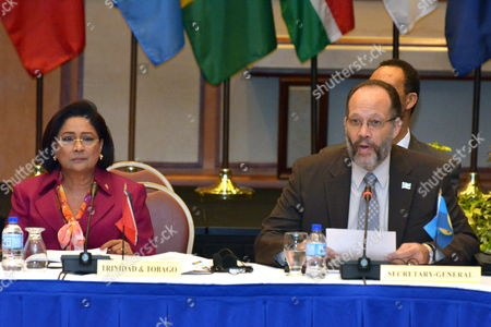 Prime Minister of Trinidad and Tobago Kamla Persad-bissessar (l) Listens As Caribbean Community (caricom) Secretary General Irwin Larocque Addresses the Opening Session of the Caricom/japan Summit at the Hilton Trinidad and Conference Centre in Port-of-spain Trinidad and Tobago 28 July 2014 Trinidad and Tobago Port-of-spain